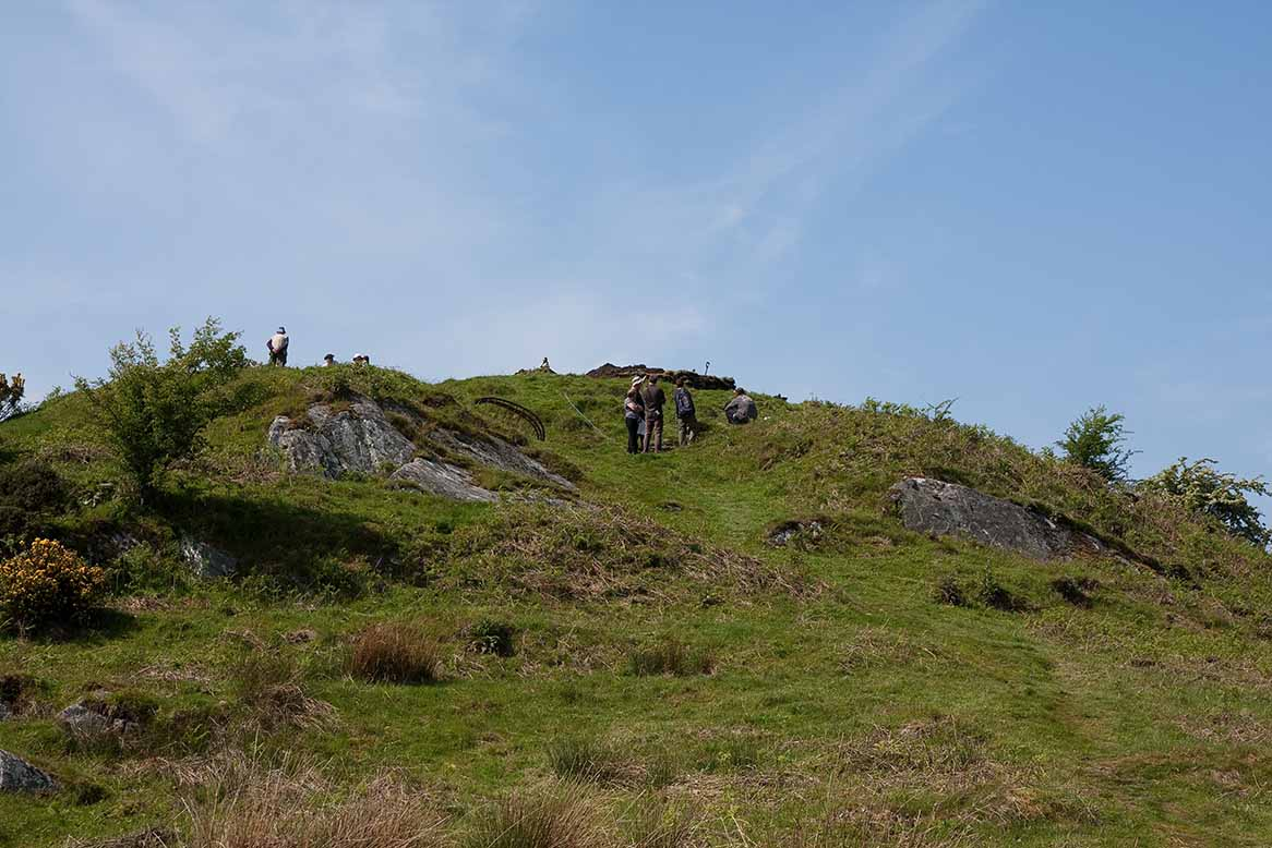 entranceway to the summit of Trusty's Hill, the carvings lie under the iron cage seen on the left, while the rock-cut basin lies to the right beyond the group of people
